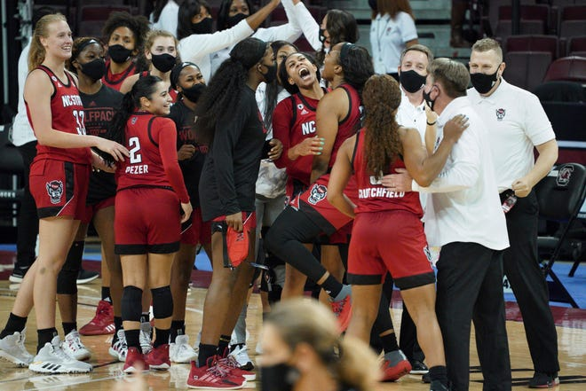 North Carolina State players celebrate with the coaching staff after  a victory against No. 1-ranked South Carolina Thursday, Dec. 3, 2020, in Columbia, S.C.