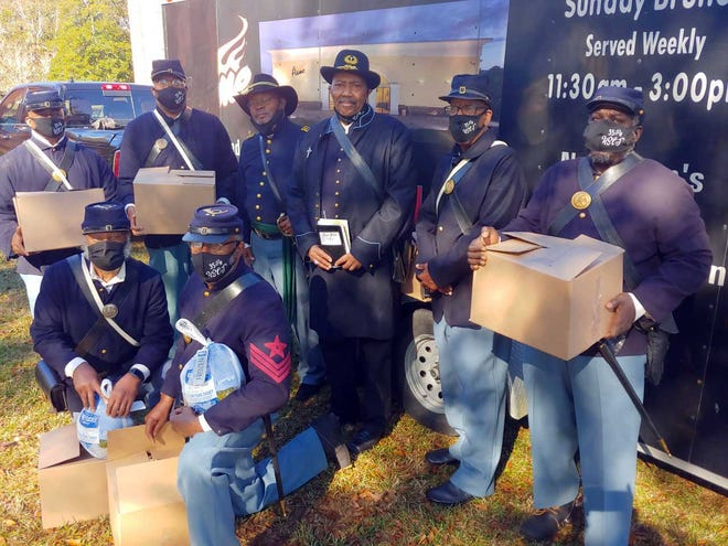 Members of the 35th Regiment United States Colored Troops Interpretive Reenactment Group at Tryon Palace gave out about 100 Thanksgiving dinner boxes on the grounds of New Bern Academy. Members pictured include Curtis Jenkins, William Davis Jr., Bernard George, Marshall Williams, William Hollowell Jr., Vernon Guion, Donald Harmon and Craig Allen. [CHARLIE HALL / SUN JOURNAL]