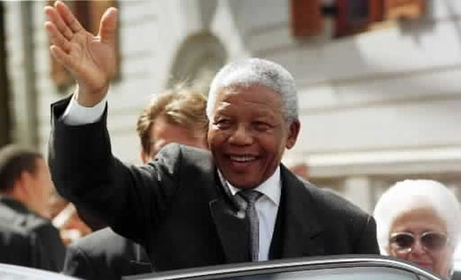 South African President Nelson Mandela waves to supporters outside Parliament in Cape Town Friday March 26, 1999.