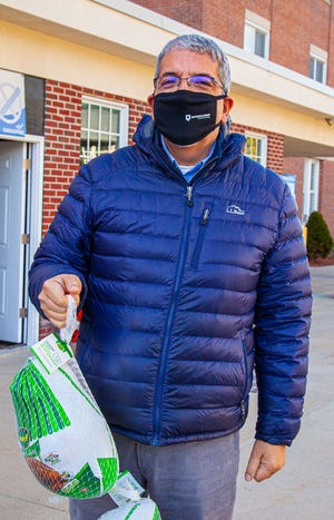Quinsigamond Community College President Dr. Luis G. Pedraja carries turkeys to students' cars during a College Food Pantry distribution. QCC distributed 40 turkeys with all the fixings to students in need for the Thanksgiving holiday.