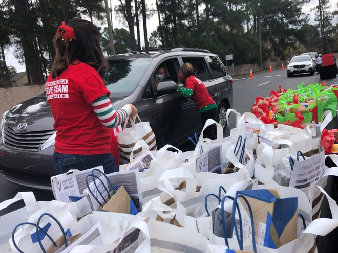 Erica Cook and Tammy Logan, part of Manna Church's Serve Team, hand out bags donated by Support Military Families on Friday at Manna Church's Cliffdale site.