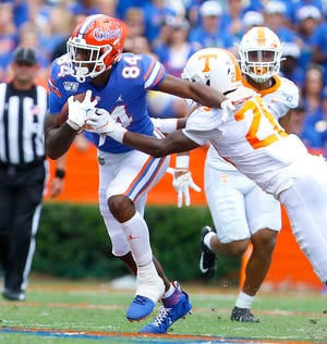 Florida tight end Kyle Pitts tries to shake a Tennessee defender after making a catch during last year's game at Ben Hill Griffin Stadium. The Gators beat the Volunteers 34-3.