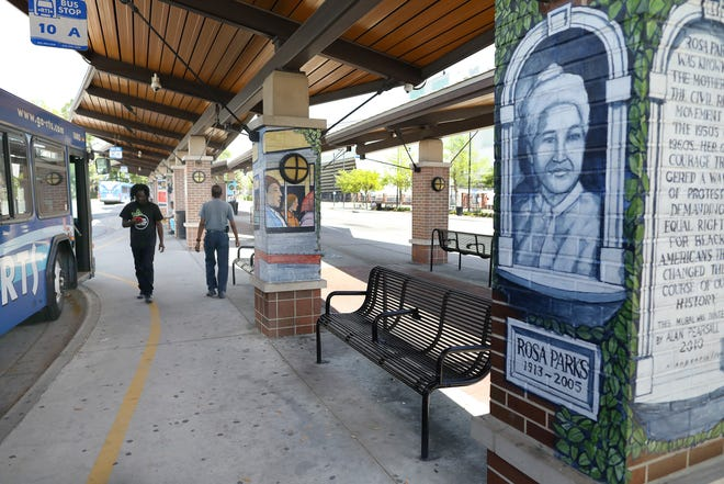People walk around the Regional Transit System Rosa Parks Transfer Station off Southeast Third Street in Gainesville in March.