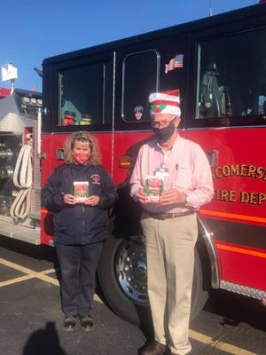 Heather Stein-Wells, l, of the Newcomerstown Emergency Rescue Squad, and Roger Seitz, of Baker's IGA in Newcomerstown, are two of the people helping Santa Claus make a visit to Newcomerstown.