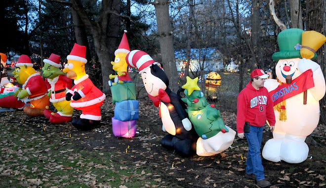 Richard Webb of Newcomerstown walks next to a few of his 140 Christmas inflatables. Each evening at 5 p.m. his yard becomes an incredible holiday scene.