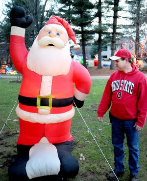 Richard Webb of Newcomerstown is pictured next to the first inflatable ever purchased for the holiday display on Bridge Street.