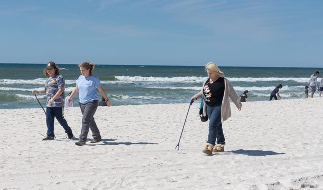 Keep PCB Beautiful volunteers sweep the beach duriing the Leap Day Cleanup.