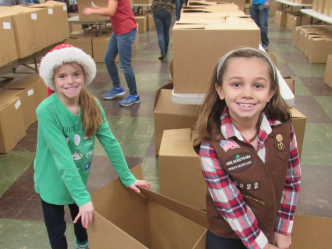 Claire Bills (left) and Laney Smith take a brief break Dec. 14, 2019, as they joined more than 100 other volunteers in filling about 375 boxes with food for Boulevard Presbyterian Church's annual Community Christmas Box project. Because of COVID-19 restrictions, three shifts of 10 volunteers each will pack boxes Dec. 11 and 12 for the 2020 project.
