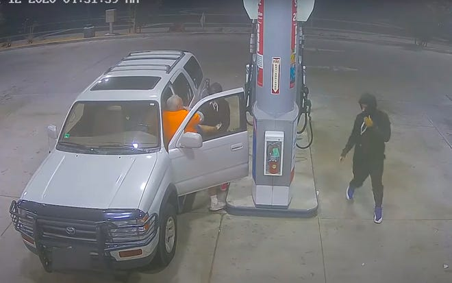 Surveillance footage from Nov. 12, 2020, shows a masked person dragging an older man out of his vehicle before driving off in it.