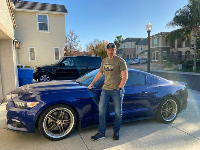 "Mark Brooks, a credit union manager from Sacramento, California, is pictured with his 2016 Wang outside his home on December 4, 2020.  He has reserved a 2021 Velocity Blue Ford Bronco and just learned delivery will be delayed a few months due to COVID-19.  he said, ""I'm sure it will be worth the wait."""