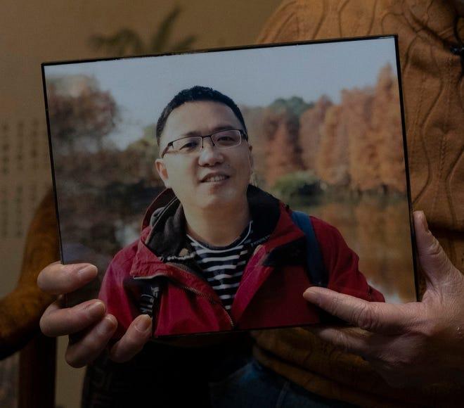 Zhong Hanneng memegang foto putranya, Peng Yi, dan berbicara tentang kesulitannya dalam menjalani tes COVID-19, yang akhirnya meninggal karena penyakit tersebut, di Wuhan di provinsi Hubei China tengah pada hari Sabtu, 17 Oktober 2020.