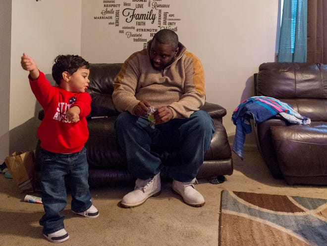 Floyd Edwards watches his two-year-old son Jakari Edwards dance in their living room Saturday afternoon, Nov. 21, 2020. Edwards recently moved into a three-bedroom house paying $600 a month. Before that, he was in a long struggle to find housing and had to live with his parents for an extended time.