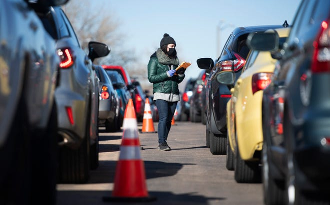 A healthcare worker speaks to motorists in line at a Larimer County COVID-19 testing site at Colorado State University in Fort Collins, Colo. on Thursday, Dec. 3, 2020.