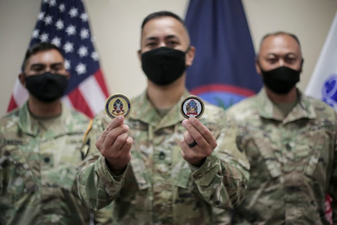 Sgt. 1st Class Brian Cruz, center, an instructor with the Guam National Guard's 203rd Regional Training Institute, was awarded coins of excellence from Lt. Col Jumar Castro, left, and acting state Command Sgt. Maj. Celso Leonen Nov. 24.