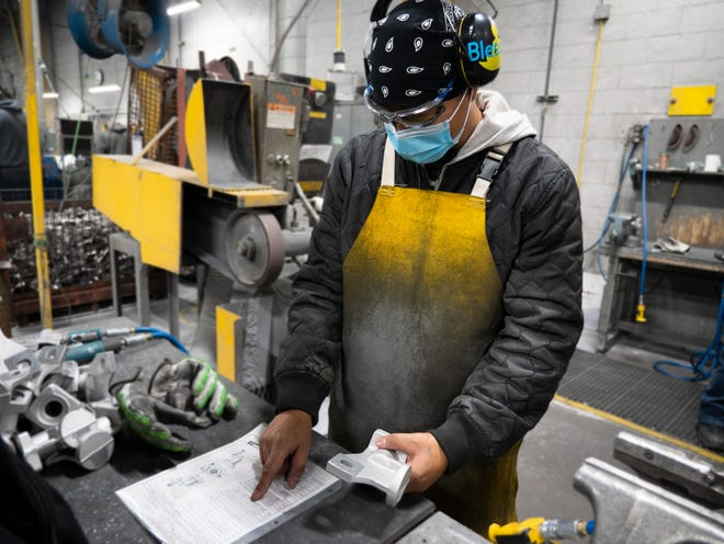 A worker at Wisconsin Aluminum Foundry in Manitowoc, wearing a mask amid the coronavirus pandemic, reads a print.