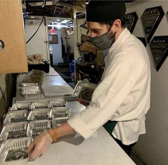 Justin Aprahamian, chef and owner of Sanford restaurant, prepares aluminum takeout containers to be filled for the Thanksgiving meal the restaurant sold this year, Sanford's first. Thanksgiving was an unexpected success for restaurants offering meals to go this year, many for the first time, because of people quarantining during the pandemic.