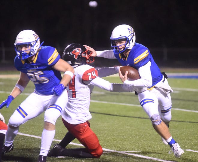 Mountain Home quarterback Bryce McKay gets past a Russellville defender as running back Gage Hershberger blocks earlier this season. McKay and Hershberger combined for 2,390 rushing yards this season for the Bombers.