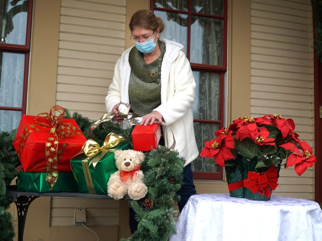 Maureen Casey places some holiday decorations on the porch of Greenmead's Alexander Blue House on Dec. 4, 2020. Greenmead will be hosting some holiday COVD-safe gatherings for the holidays in the coming weekends. Casey is the Recreation Supervisor for the City of Livonia.