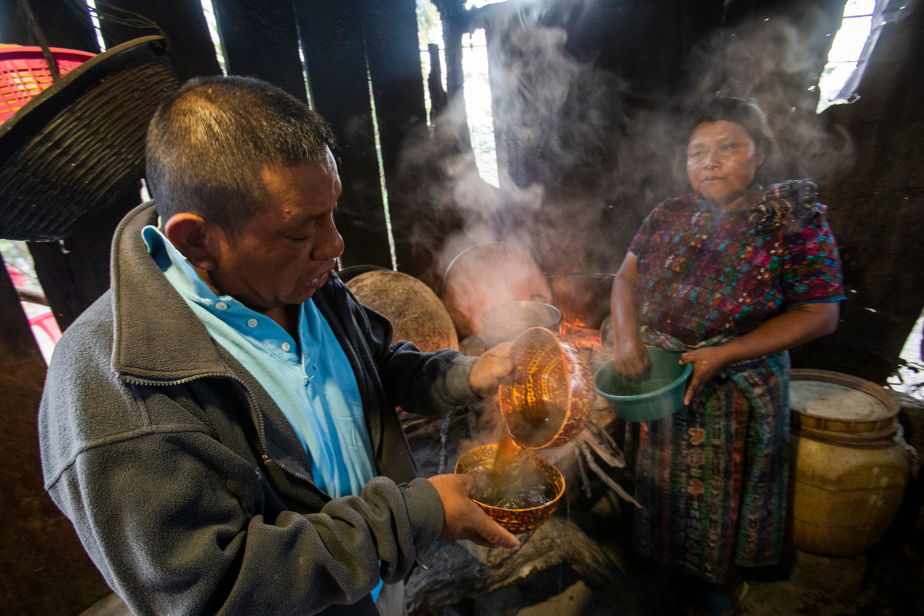 Maria Elvira Ramos serves her husband, Francisco Sical, coffee in a traditional Mayan bowl in early March. Her outdoor kitchen is flanked with timber. Sical promised her a kitchen of cement block with money he would make working in the USA, a dream he gave up in summer 2019.