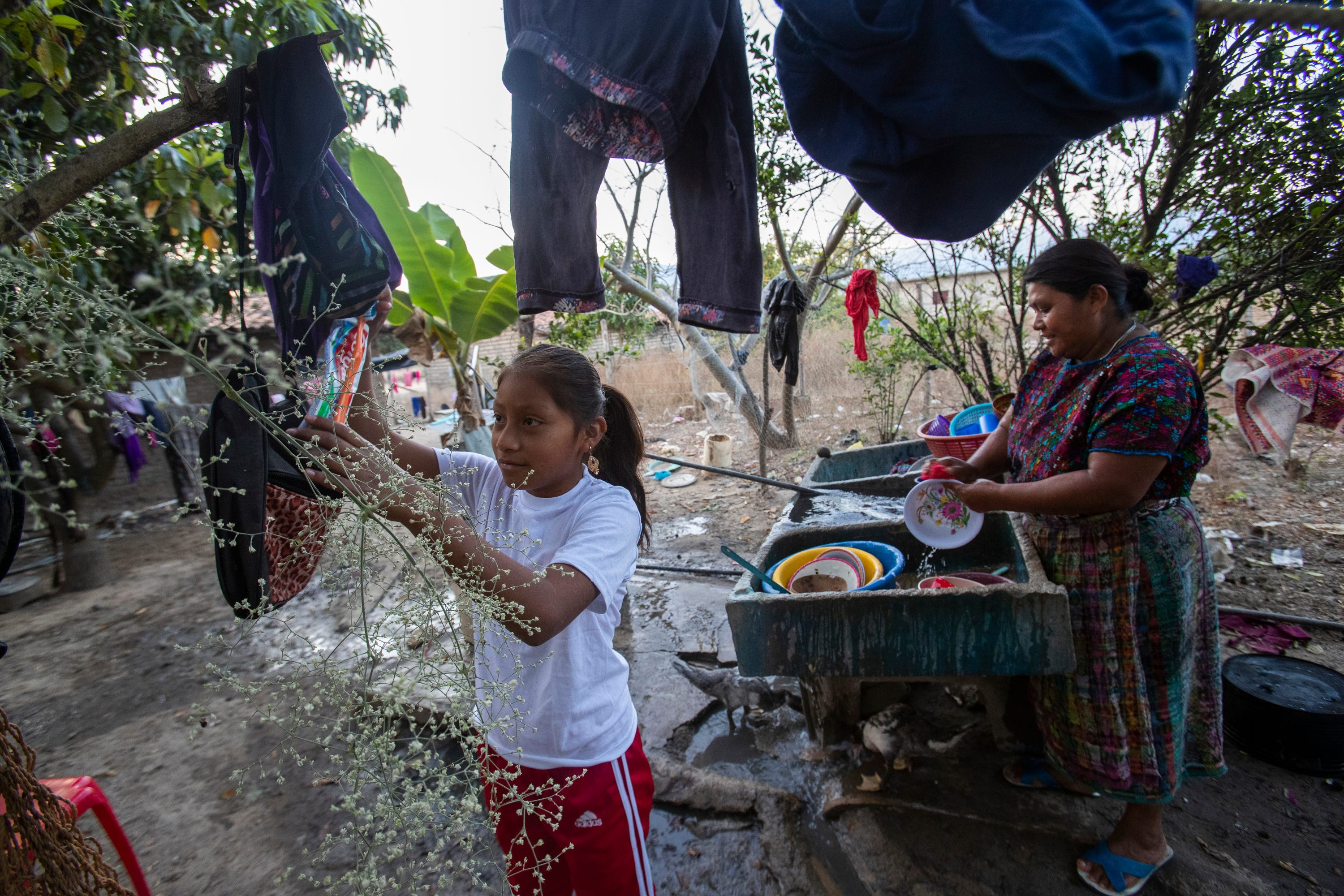 Melissa Sical and her mother, Maria Elvira Ramos, use well water to wash dishes in Baja Verapaz, Guatemala, in early March. Melissa and her father traveled to the U.S. border during the summer of 2019, where they were subjected to the Migrant Protection Protocols and required to wait in Juárez two months for a U.S. court hearing.