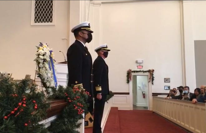 Capt. Edgardo Moreno and Rear Adm. Pete Garvin stand at attention next to a wreath place in memory of the killed and injured in the attack on NAS Pensacola one year ago.