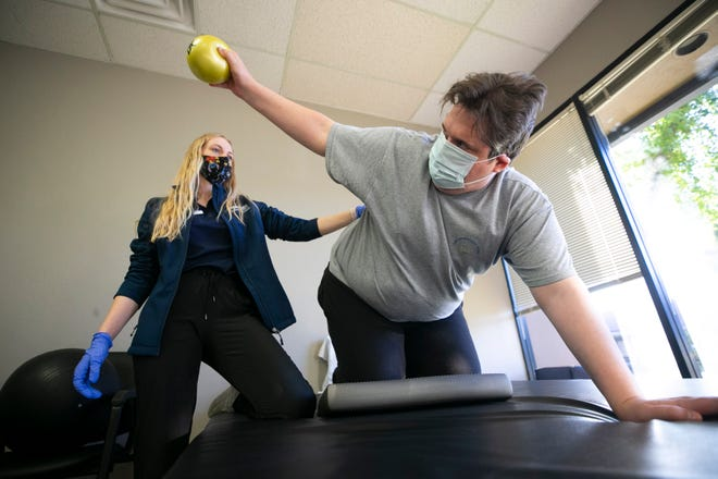 An occupational therapist works with a patient who suffered a traumatic brain injury from a shooting and has relied on therapy to relearn how to do basic things.
