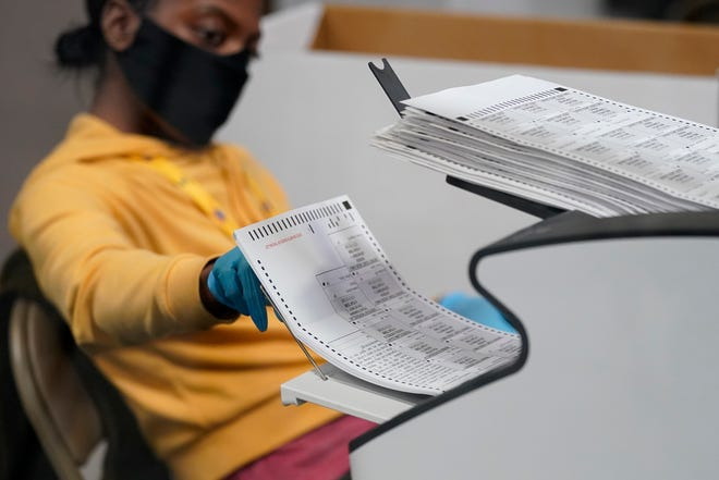 A county election worker scans mail-in ballots at a tabulating area at the Clark County Election Department in Las Vegas on Nov. 5.
