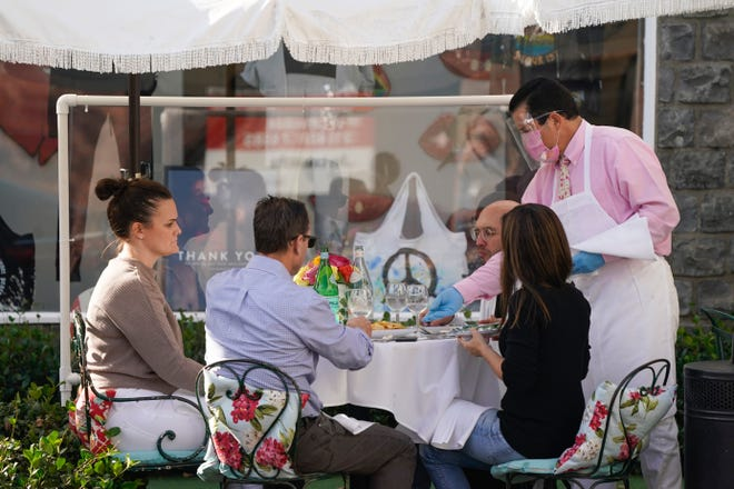 In this Nov. 18, 2020, file photo, diners are served outside by a waiter wearing a mask, face shield and rubber gloves in West Hollywood, Calif. With coronavirus cases surging at a record pace, California Gov. Gavin Newsom announced a new stay-at-home order Thursday, Dec. 3, 2020, and said if people don't comply, the state's hospitals will be overwhelmed with infected patients.