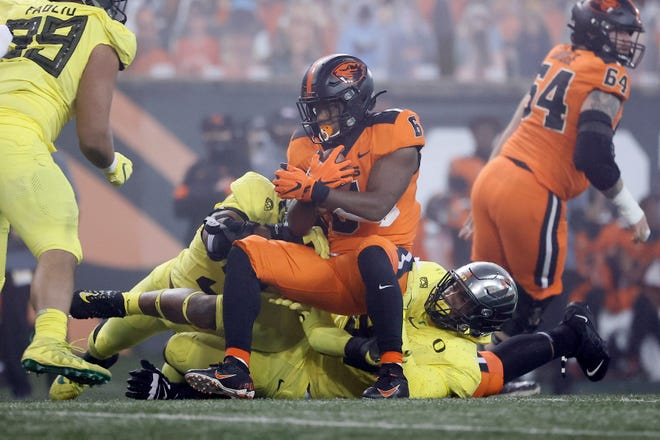 Nov 27, 2020; Corvallis, Oregon, USA; Oregon State Beavers running back Jermar Jefferson (6) is brought down by Oregon Ducks defensive tackle Brandon Dorlus (right) and defensive end Kayvon Thibodeaux (left) during the first half at Reser Stadium. Mandatory Credit: Soobum Im-USA TODAY Sports