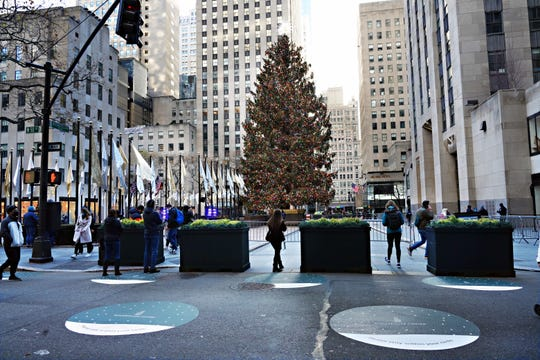 People stop to look at the Rockefeller Center Christmas Tree on Dec. 3, 2020, in New York City.