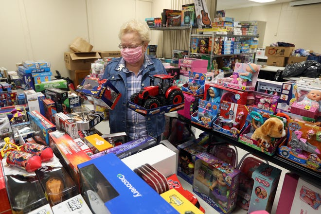 Beth Archer, president of Zanesville's Salvation Army Women's Auxiliary group, chooses toys for a child in the Salvation Army's Angel Tree program. The auxiliary is trying to provide a brighter Christmas to more than 700 children with the help of volunteers and donations.