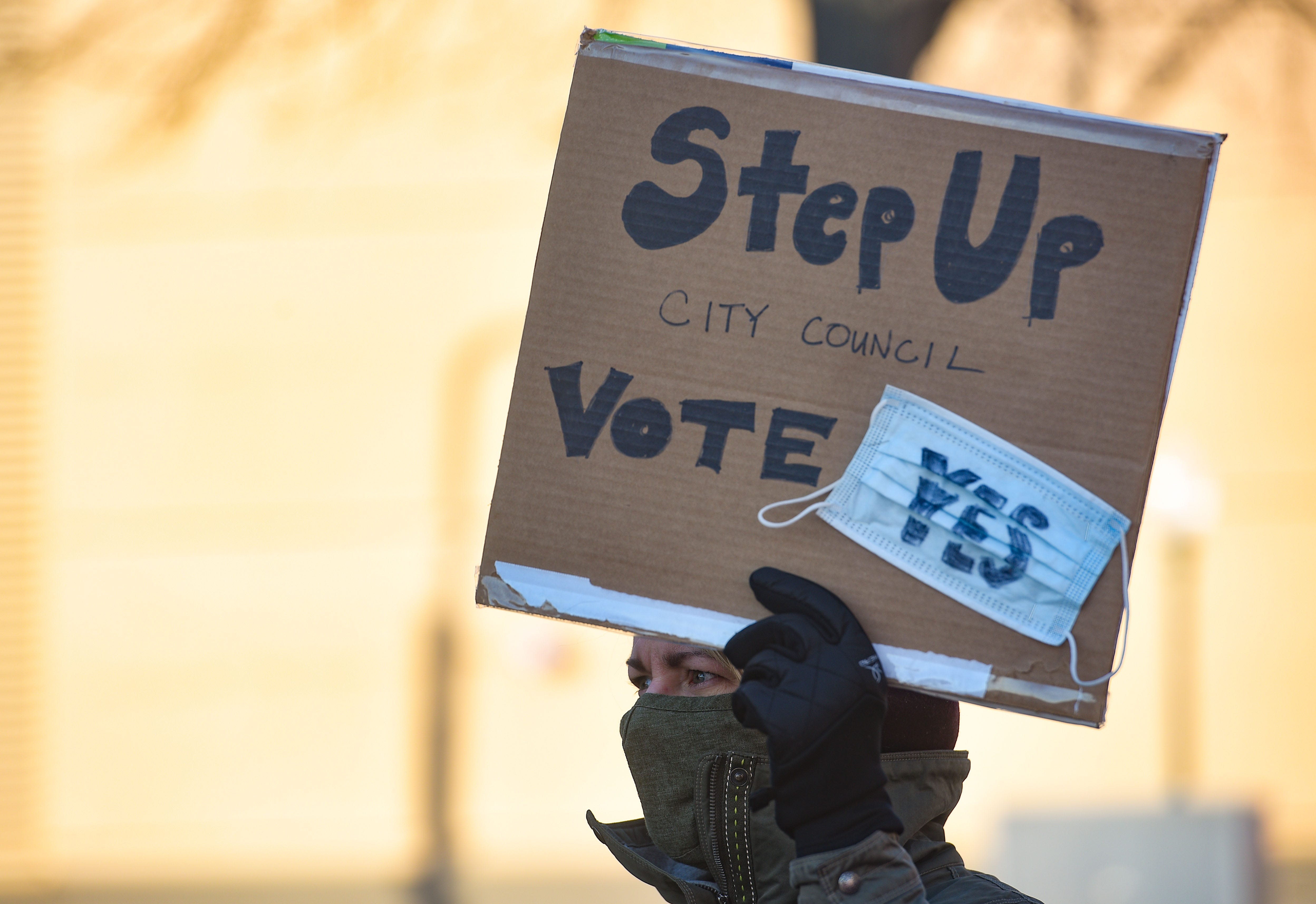 A demonstrator holds a sign demanding a mask mandate from the city council on Monday, November 16, outside Carnegie Town Hall in Sioux Falls.