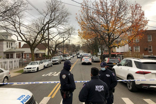 New York Police officers block off the street near the scene where a suspect was killed during a shootout with U.S. marshals in the Bronx that left two officers wounded, Friday, Dec. 4, 2020, in New York. The suspect, 35-year-old Andre Sterling, was wanted for shooting a Massachusetts state trooper in the hand on Nov. 20 during a traffic stop in Hyannis, Mass.