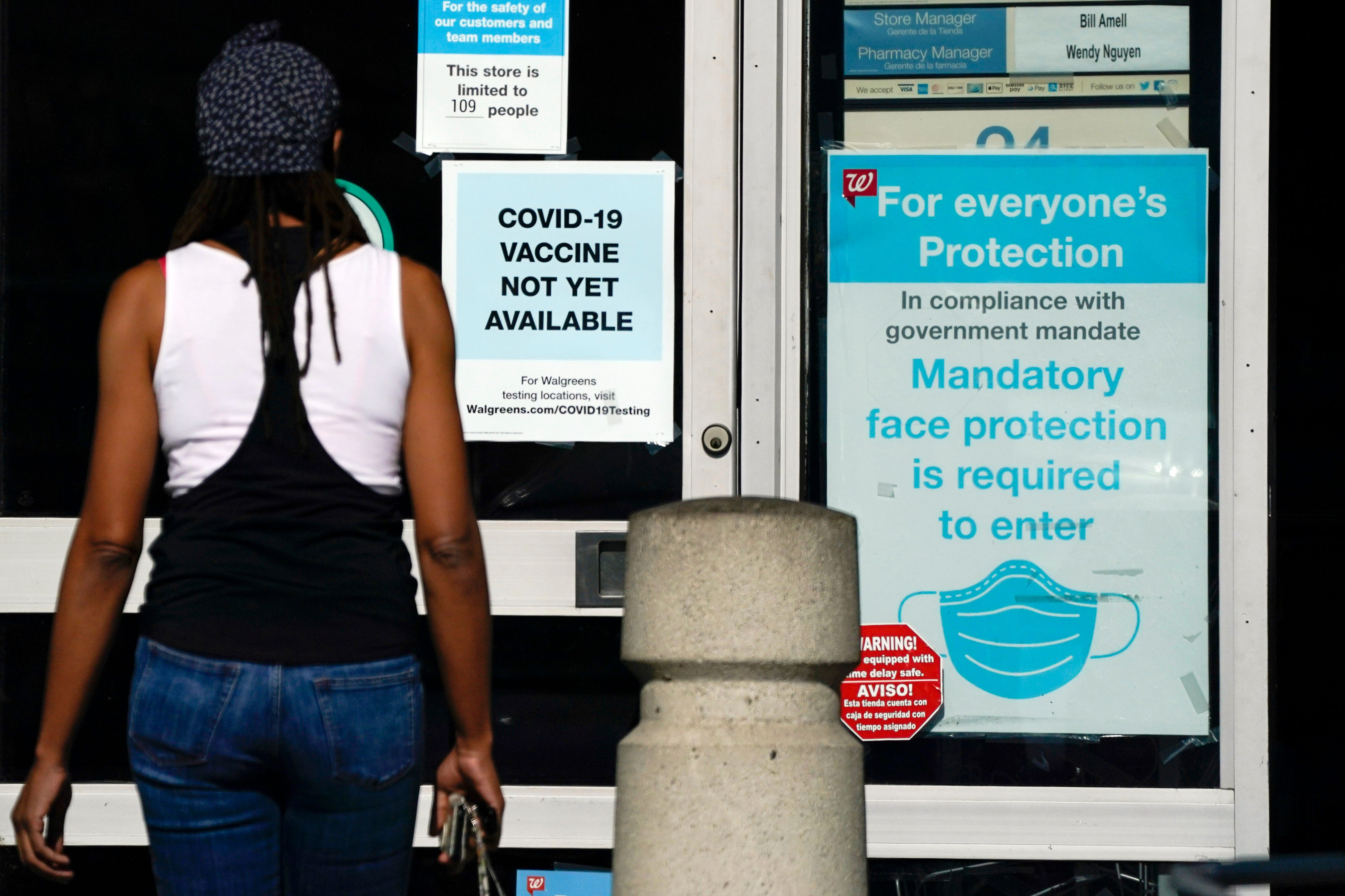 A customer walks past a sign on Dec. 2 indicating a COVID-19 vaccine is not yet available at a Walgreens in Long Beach, California. States faced a deadline of Dec. 4 to place orders for the coronavirus vaccine as many reported record infections, hospitalizations and deaths, while hospitals were pushed to the breaking point with the worst feared yet to come.