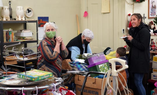 Sharon DuBois, in the green mask, chats with an unmasked customer in thrift shop she runs, after her mother passed away from COVID-19 at the nursing home at the Gove County Medical Center.