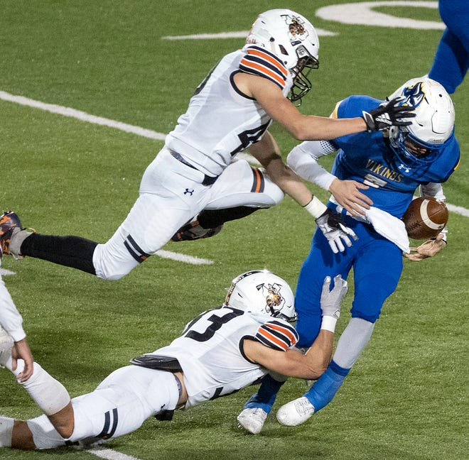 Lago Vista's Adrian Hernandez, right, fumbles the ball after Llano's Hayden Manahan, left, strips it away while Austin Hulon helps on the tackle during Llano's 31-25 playoff win Friday in Leander.