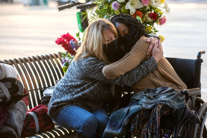 Sheila Foster, left, mother to Garrett Foster, embraces Garrett's fiancee Whitney Mitchell on Friday as they return to the intersection where he was fatally shot on East Fourth Street and Congress Avenue.