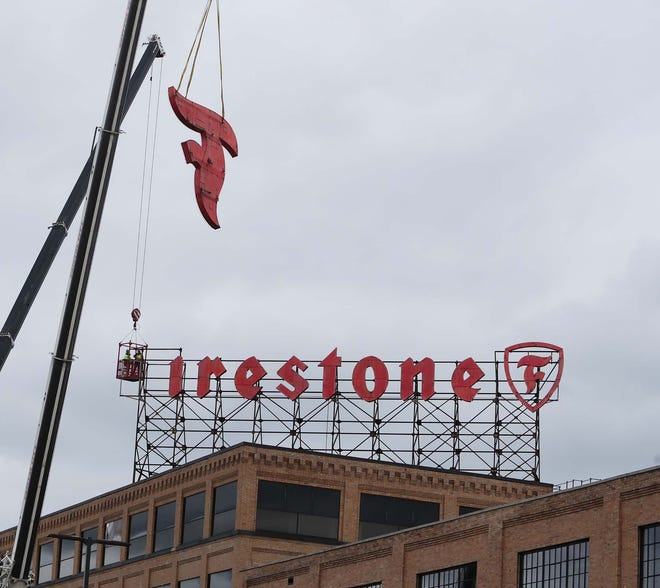 The iconic Firestone sign atop Building One is being removed letter by letter then the symbol Saturday, Dec. 5, 2020 in Akron, Ohio. Bridgestone Americas is upgrading the sign from neon lights to LED lights and it will be refurbished and then relocated.