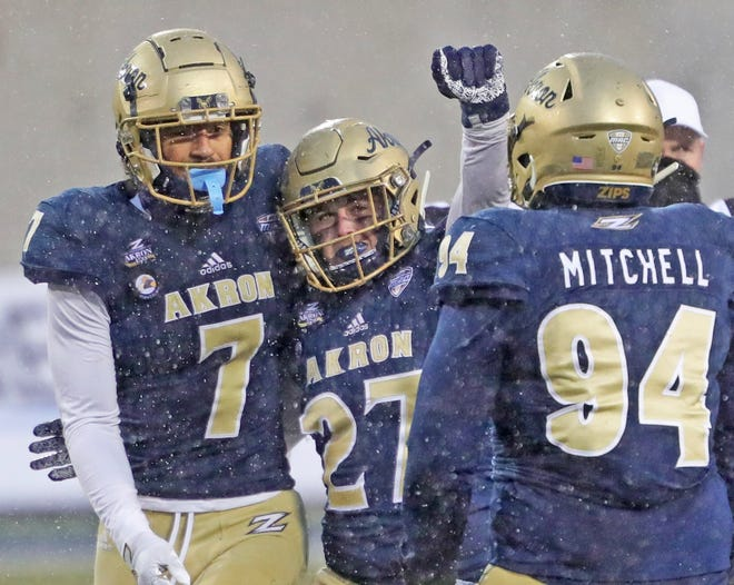 University of Akron linebacker Bubba Arslanian (27) celebrates with teammates after sacking Bowling Green quarterback Matt McDonald during the second half of Saturday's game at InfoCision Stadium. The Zips ended a 21-game losing streak with a 31-3 win over the Falcons. [Jeff Lange/Beacon Journal]