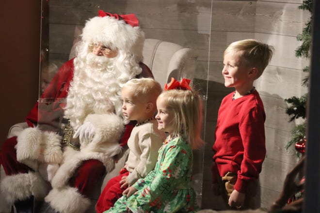 Huck, Scout and Know Jones stop to take a photo with Santa at the Don Harrington Discovery Center Santa's Jolly Jamboree Saturday morning.  [Neil Starkey / For the Amarillo Globe-News]