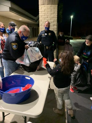 Children pick up their gifts from Ardmore police officers Friday evening at Shop with Cops. Typically the children go to the store with police to select their gifts, but this year police bought items off of wish lists.