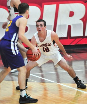 Loudonville's Jacob Gessner (10) defends Temple Christian's Micah Simpson (12) during boys basketball action Friday at Loudonville High School. The Redbirds defeated the Crusaders, 74-46.