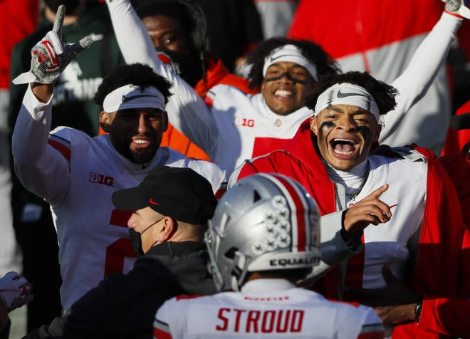 Ohio State players including Chris Olave (2) and Justin Fields (1) celebrate a fourth-quarter touchdown run by backup quarterback C.J. Stroud.