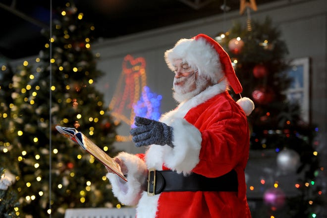 Santa Claus (Father John French) wears a face mask as he reads a book during the Santa VIP Experience at Heritage Museums & Gardens' Garden Aglow last month. The museum is collecting unwrapped toys for the Toys for Tots program.