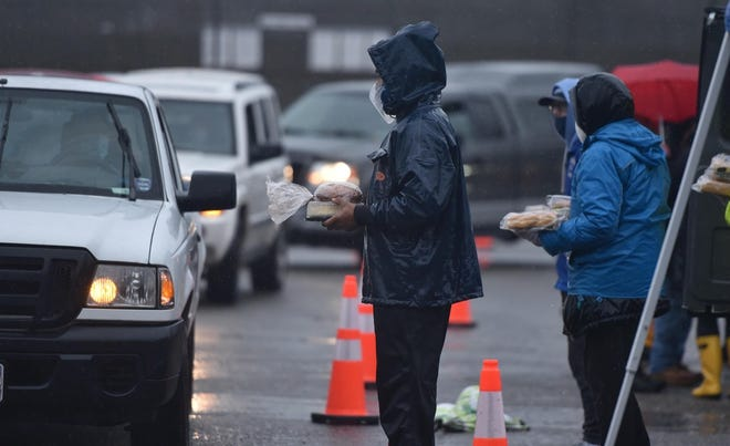 State Rep.-elect Kip Diggs, center, staffs the line for the weekly food give away at Cape Cod Community College in West Barnstable as cars line up in a steady rain for the food on Saturday. Nearly 900 food boxes were distributed.