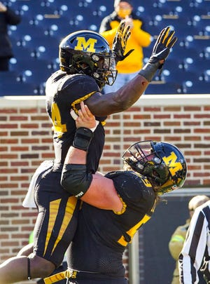 Missouri running back Larry Rountree (34) celebrates with offensive lineman Case Cook (59) after scoring a touchdown against Arkansas during a game Saturday at Faurot Field.