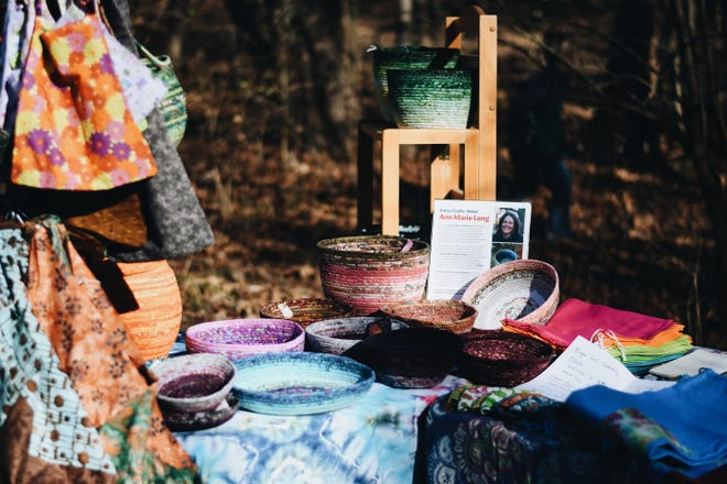 Ann Marie Long sells woven pots at the Woodland Holiday Craft Fair at the Camp Takimina campgrounds on Saturday afternoon.