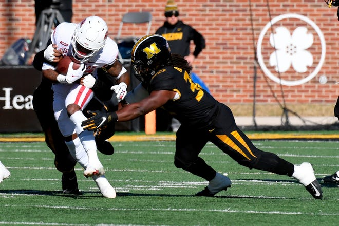Missouri linebacker Nick Bolton, right, reaches to tackle Arkansas running back Trelon Smith during a game Saturday at Faurot Field.