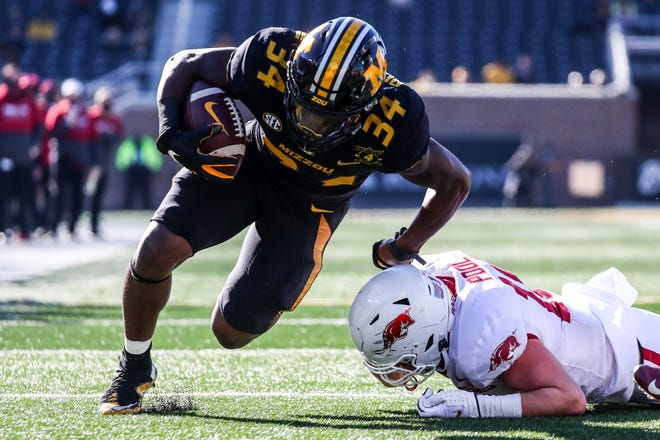 Missouri running back Larry Rountree (34) carries the ball past Arkansas linebacker Bumper Pool (10) during a game Dec. 5 at Faurot Field.