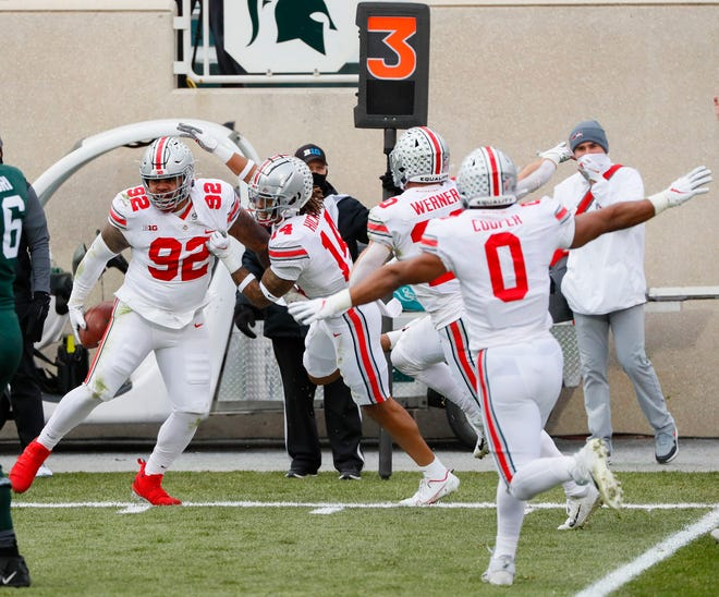 Ohio State Buckeyes defensive tackle Haskell Garrett (92) celebrates after batting the ball and recovering it as an interception in the end zone for a touchdown during the second quarter of a NCAA Division I football game between the Michigan State Spartans and the Ohio State Buckeyes on Saturday, Dec. 5, 2020 at Spartan Stadium in East Lansing, Michigan.